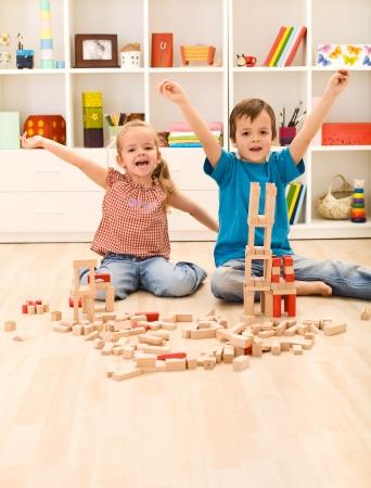 Photo pour Kids proudly showing their wooden block buildings, sitting on the floor - image libre de droit