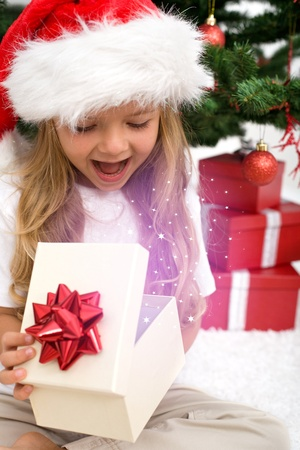 Excited little girl opening christmas present with magical glow in front of the fir tree - closeupの写真素材