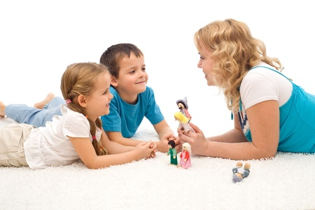 Woman telling a story to her happy kids laying on the floor and illustrating it with puppets - isolated
