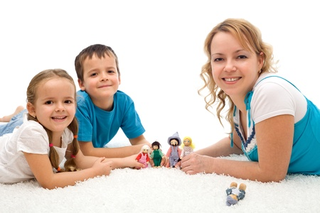 Happy woman and kids playing on the floor with puppets smiling - isolated