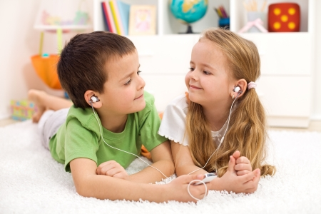 Photo pour Kids sharing earphones listening to music laying on the floor - image libre de droit