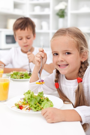 Kids in the kitchen eating healthy vegetables