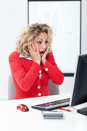 Photo pour Oh no - shocked business woman in front of computer in the office - image libre de droit