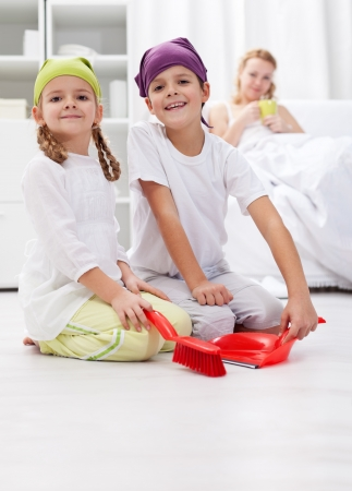 Kids cleaning the room helping  their sick  mother