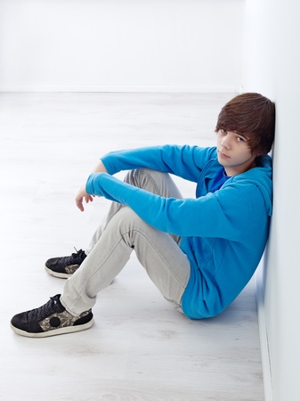 Moody teenager sitting by the wall on the floor