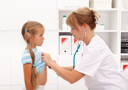 Little girl at the doctor being examined with stethoscope