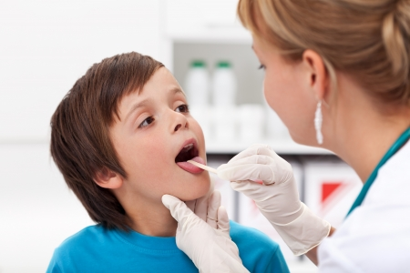 Say aaah - little boy at the physician checking his throat