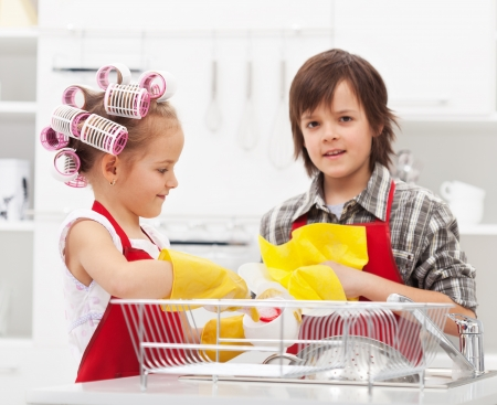 Kids doing the dishes together in the kitchen - closeup on sink area