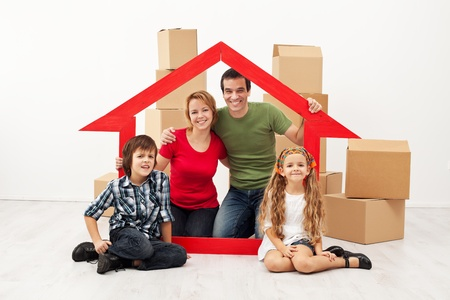 Happy family with kids moving into a new home - sitting with cardboard boxes