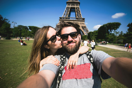 Foto de Happy smiling couple kissing and taking selfie photo in front of Eiffel Tower in Paris while traveling across France - Imagen libre de derechos