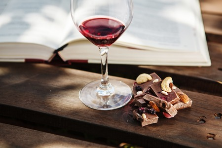 Photo pour Glass with wine and pieces of chocolate near open book - image libre de droit