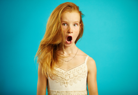Red haired girl in white dress with surprised expression opens her mouth and eyes wide, shows a strong emotion of fear or shock, is shocked and stunned.の写真素材