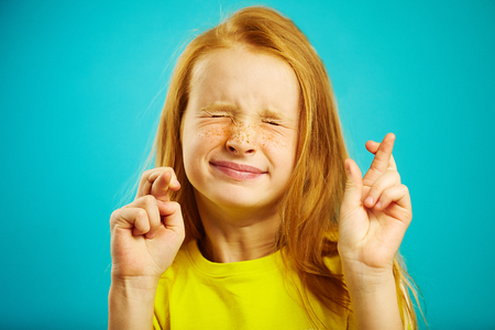 Children girl tightly closed his eyes and put fingers crossed, make a wish, believe in the dream, expresses heartfelt emotions, has funny facial features, beautiful red hair with freckles.