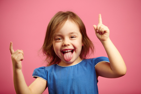 Photo pour Cheerful little girl dancing with her hands raised and tongue sticking out, portrait of joyful female child over pink background. - image libre de droit