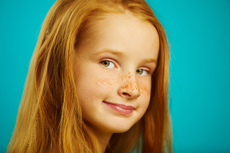 Foto de cute ten year old redheaded girl on blue isolated background, close-up shot of beautiful child with freckles. - Imagen libre de derechos