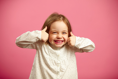 Funny shot of little girl with her thumbs up