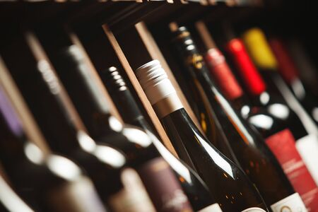 Photo for Wine cellar with elite drinks on shelves with names written on boards. Background with different expensive alcoholic beverages - Royalty Free Image