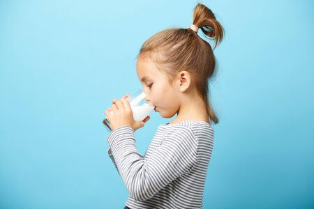 Photo for Child girl drinks milk without lactose, sideways portrait against blue isolated. - Royalty Free Image