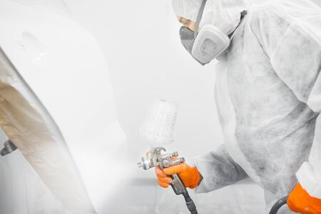 Photo pour Spray painter worker in protective glove with airbrush pulverizer painting car body in white paint chamber. - image libre de droit