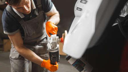 Foto de Car detailing. Close up of man with orbital polisher in auto repair shop. Bodywork maintenance. - Imagen libre de derechos