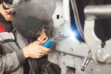 Photo pour Auto mechanic in protective mask welds car body. Metalworking with carbon dioxide welding. Concept of industry and repair bodywork. - image libre de droit