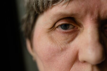 Photo for Retired woman with tired glance full of sadness looking away, extreme close-up shot - Royalty Free Image