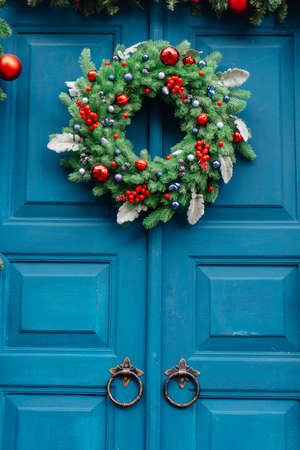 Photo pour Christmas wreath of fir branches on a blue wooden door and a garland of fir branches. - image libre de droit