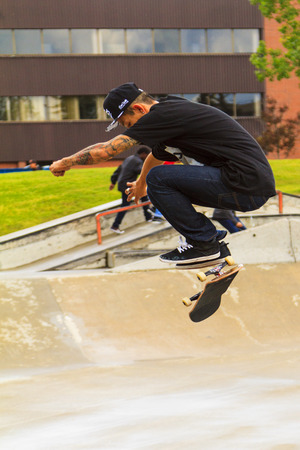 CALGARY, CANADA - JUN 21, 2015: Athletes have a friendly skateboard competition in Calgary. California law requires anyone under the age of 18 to wear a helmet while riding a skateboard.