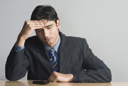 Businessman rubbing his forehead