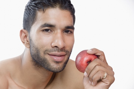Portrait of a macho man eating apple