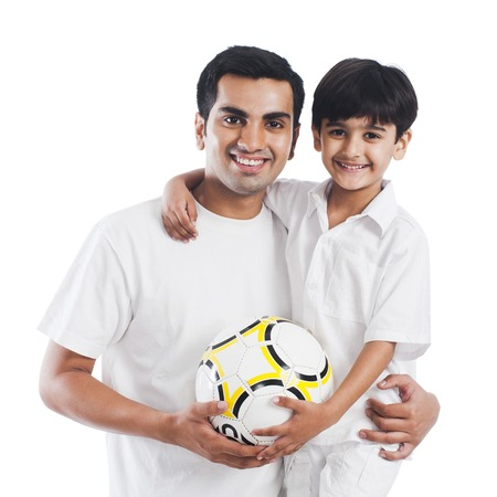 Portrait of a happy father and son with football