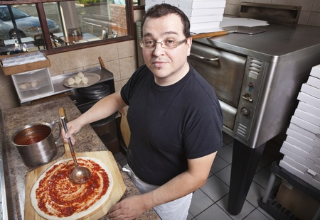 Chef making a pizza spreading sauce