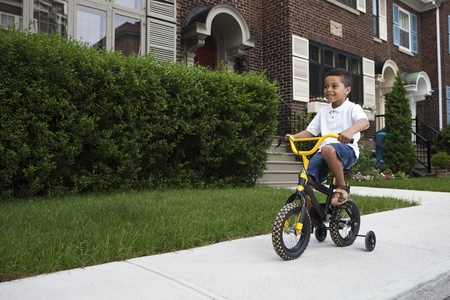 Young boy riding his first bicycle with training wheels (horizontal)