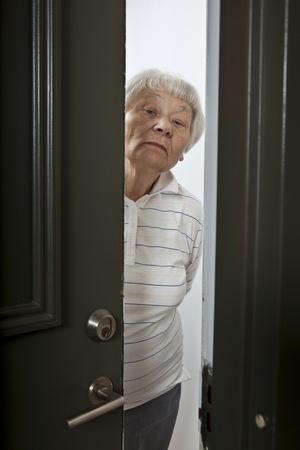 Annoyed senior woman opening front door