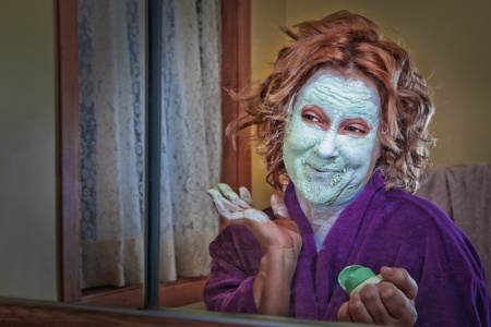Narcissistic woman looking in mirror while applying beauty cream