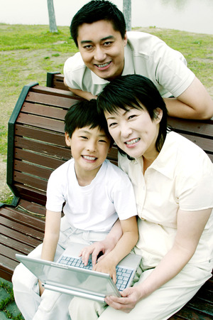 Boy using laptop with his parents