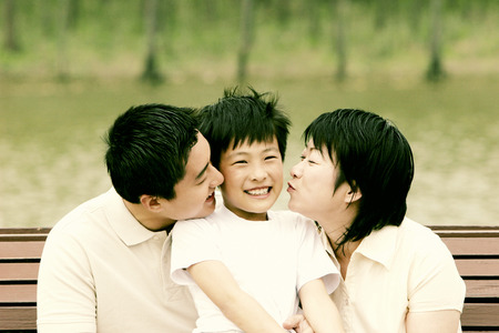 Boy getting kisses from his parents