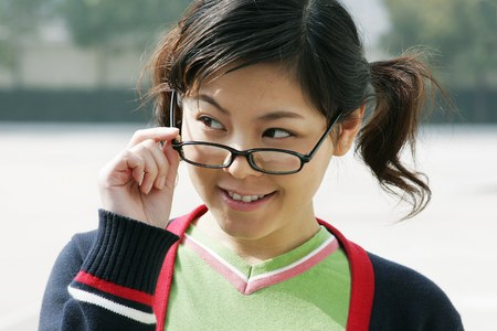 Girl smiling while adjusting her spectacles.