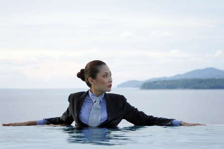 Photo pour Businesswoman in suit sitting in the swimming pool. - image libre de droit
