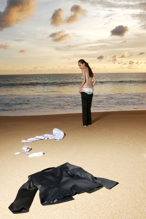 Businesswoman discarding her clothes on the beach.