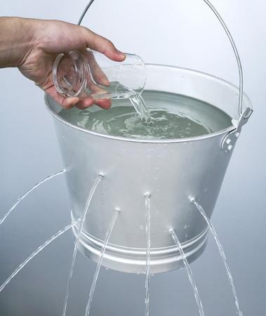 Foto für Hand pouring water from a glass into a leaking pail - Lizenzfreies Bild