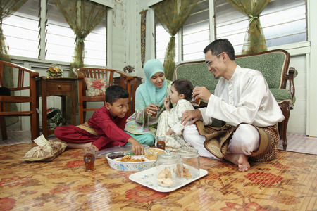 Couple and kids enjoying pastry and drinks