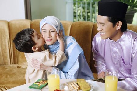 Foto de Boy kissing woman on the cheeks, man smiling - Imagen libre de derechos