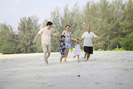 Foto de One happy family walking hand in hand on the beach - Imagen libre de derechos