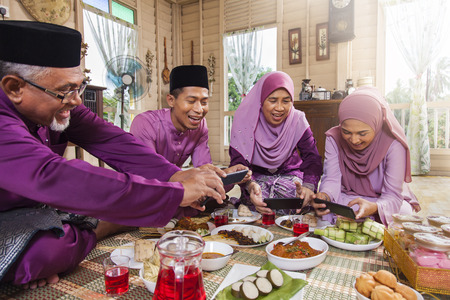 Photo for Muslim family taking pictures of food during the Eid al-Fitr - Royalty Free Image