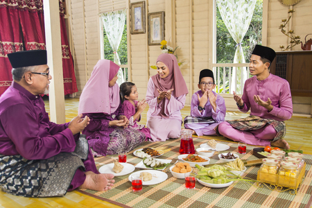 Foto de Muslim family saying prayers before meal - Imagen libre de derechos