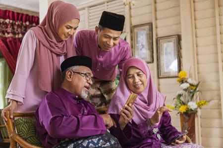 Photo pour Muslim family looking at a mobile phone - image libre de droit