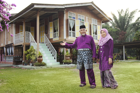 Photo for Muslim couple standing outside their house - Royalty Free Image