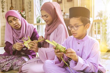 Photo pour Muslim family weaving ketupat - image libre de droit
