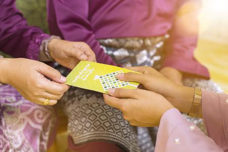 Photo pour Muslim woman receiving green envelope from senior woman during Eid al-Fitr - image libre de droit